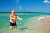 Happy mature man splashing the water on beach — Stock Photo