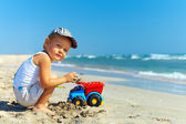 Beautiful little boy playing on the beach — Stock Photo