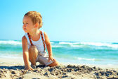 Thoughtful baby boy sitting on the beach — Stock Photo