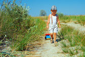 Cute baby boy walking the field path, dragging toy car — Stock Photo