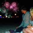 Young couple watching colorful fireworks at the beach — Stock Photo