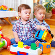 Stock Photo: Two cute baby toddlers playing in nursery room