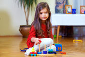 Beautiful little girl playing toys at home — Stock Photo