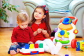 Cute babies playing toys at home — Stock Photo