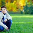 Stylish teenage boy in green park — Stock Photo