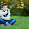 Thoughtful teenager boy in green park — Stock Photo #20503585