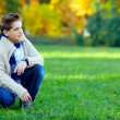 Stylish teenage boy on green meadow — Stock Photo