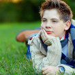 Portrait of handsome teenager on green grass — Stock Photo
