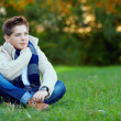 Portrait of handsome teenager boy on green grass — Stock Photo