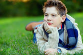 Portret van knappe tiener op groen gras — Stockfoto