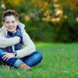 Smiling teenage boy on green lawn — Stok fotoğraf