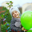 Happy kid boy playing outdoors with balloon - Stock Photo