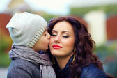 Portrait of cute kid kissing mother — Stockfoto