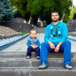 Stock Photo: Similar father and son sitting on stairs in park