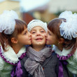 Cute twin girls kissing happy boy - Foto Stock