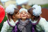 Cute twin girls kissing happy boy — Stock Photo