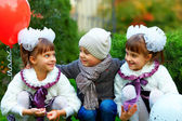 Happy twin girls and boy, colorful outdoors — Stock Photo