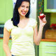 Happy woman eating apple, kitchen interior — Stock Photo