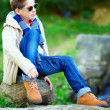 Stylish teenage boy sitting on rock outdoors — 图库照片