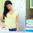 Happy young woman ironing clothes at home — Stock Photo
