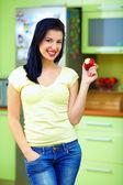Smiling woman eating apple, kitchen interior — Stock Photo