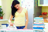 Smiling woman ironing clothes at home — Stock Photo