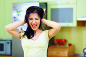 Angry woman screaming in kitchen, home interior — Stock Photo