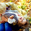 Stock Photo: Playful mother and baby having fun in autumn park