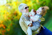 Happy mother and baby playing in colorful park — Stock Photo