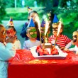Royalty-Free Stock Photo: Happy kids around birthday cake