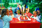Happy kids around birthday cake — Stock Photo