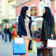 Beautiful elegant women walking the crowded city street with shopping bags — Stock Photo