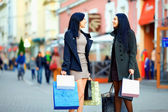 Beautiful elegant women walking the crowded city street with shopping bags — Stockfoto