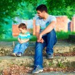 Royalty-Free Stock Photo: Father and son talk, while sitting on old stairs among trees