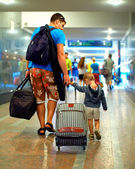 Father and son walking through crowded subway with huge luggage — Stock Photo