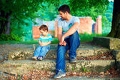 Father and son talk, while sitting on old stairs among trees — Stock Photo