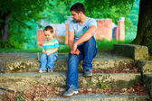 Father and son talk, while sitting on old stairs outdoor — Stok fotoğraf