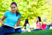 Beautiful female student on green lawn — Stock Photo