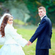 Portrait of wedding couple holding hands in park — Stock Photo