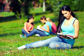 Beautiful student girl on colorful sunny lawn — Stock Photo