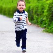 Stock Photo: Happy baby boy in motion, running the spring street