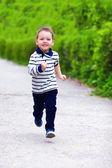 Happy baby boy in motion, running the spring street — Stock Photo