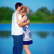 Beautiful young couple in love dating near the lake — Stock Photo
