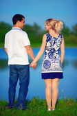 Young couple in love holding hand, near the lake — Stock Photo