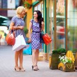 Beutful young women walking the city stores, shopping — Stock Photo