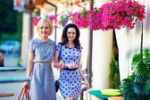 Two smiling woman friends walking the summer city — Stock Photo