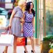 Two smiling woman looking in shop window, colorful exterior — Stock Photo #25313553