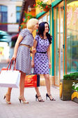 Two smiling woman looking in shop window, colorful exterior — Stock Photo