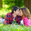 Beautiful couple in love lying on green grass — Stock Photo