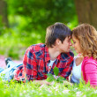 Beautiful young couple in love lying in spring grass — Stock Photo